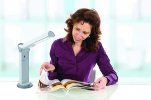 Grown woman with long brunette hair sitting at a desk and reading a book in front of white background.